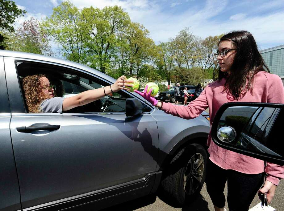 Samantha Restivo hands a softball back to Devon Yaghmaie after signing it prior to joining a caravan of players, former teammates and friends to parade pass the homes of Stamford High School's Class of 2020 senior softball players Emily Ferretti and Morgan Yacavone, led by their coach Melissa Giordano, Thursday, May 14, 2020 in Stamford, Connecticut. With the Lady Black Knights season cancel, due to school closings in response to the Covid-19 Pandemic, Giordano wanted to recognize her two seniors and their accomplishments. Emotions and excitement ran high with both players crying with joy, receiving cards, a signed ball and a lot of virtual hugs, as the players and friend practice responsible social distancing. Stamford Police provided an escort, so that participants could safely travel from one players home to the other, provide an occasional blast from the sirens. Photo: Matthew Brown / Hearst Connecticut Media / Stamford Advocate