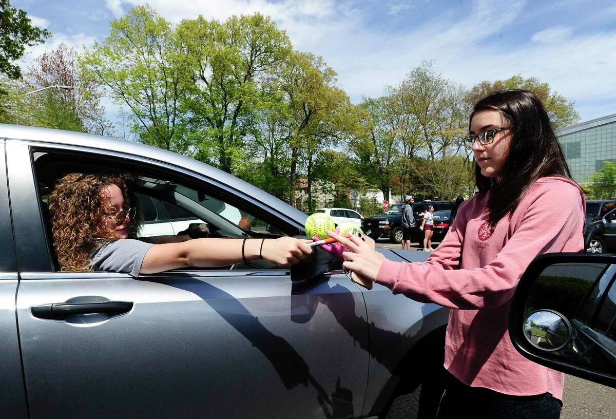 Samantha Restivo hands a softball back to Devon Yaghmaie after signing it prior to joining a caravan of players, former teammates and friends that paraded past the homes of Stamford High School's Class of 2020 senior softball players Emily Ferretti and Morgan Yacavone, led by their coach Melissa Giordano, Thursday, May 14, 2020 in Stamford, Connecticut.