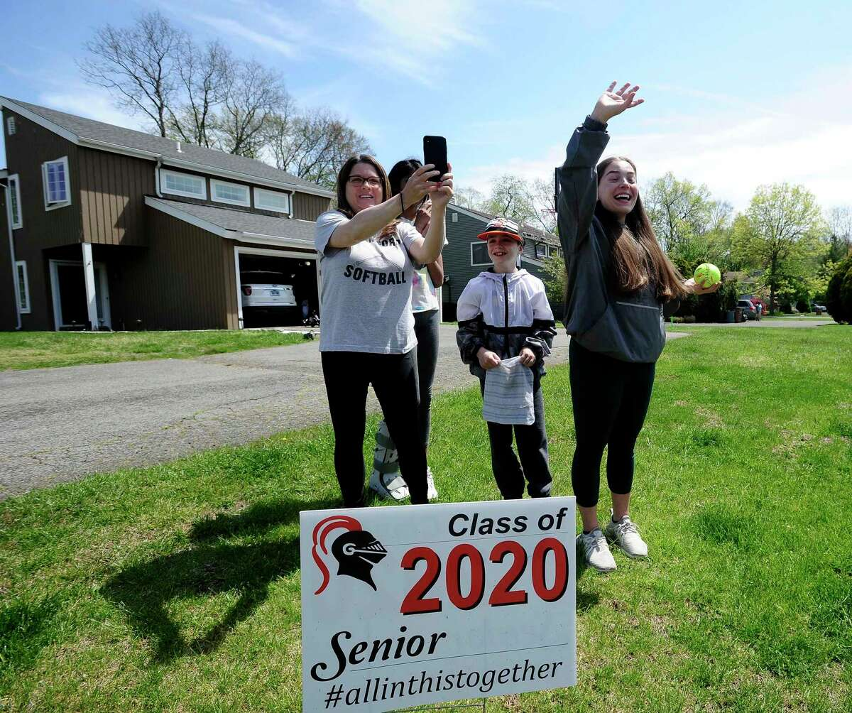 Emily Ferretti's mother Lisa captures the moment as her daughter waves as a caravan of players, former teammates and friends parade pass the homes of Stamford High School's Class of 2020 senior softball players Emily Ferretti and Morgan Yacavone, led by their coach Melissa Giordano, Thursday, May 14, 2020 in Stamford, Connecticut. With the Lady Black Knights season cancel, due to school closings in response to the Covid-19 Pandemic, Giordano wanted to recognize her two seniors and their accomplishments. Emotions and excitement ran high with both players crying with joy, receiving cards, a signed ball and a lot of virtual hugs, as the players and friend practice responsible social distancing. Stamford Police provided an escort, so that participants could safely travel from one players home to the other, provide an occasional blast from the sirens.