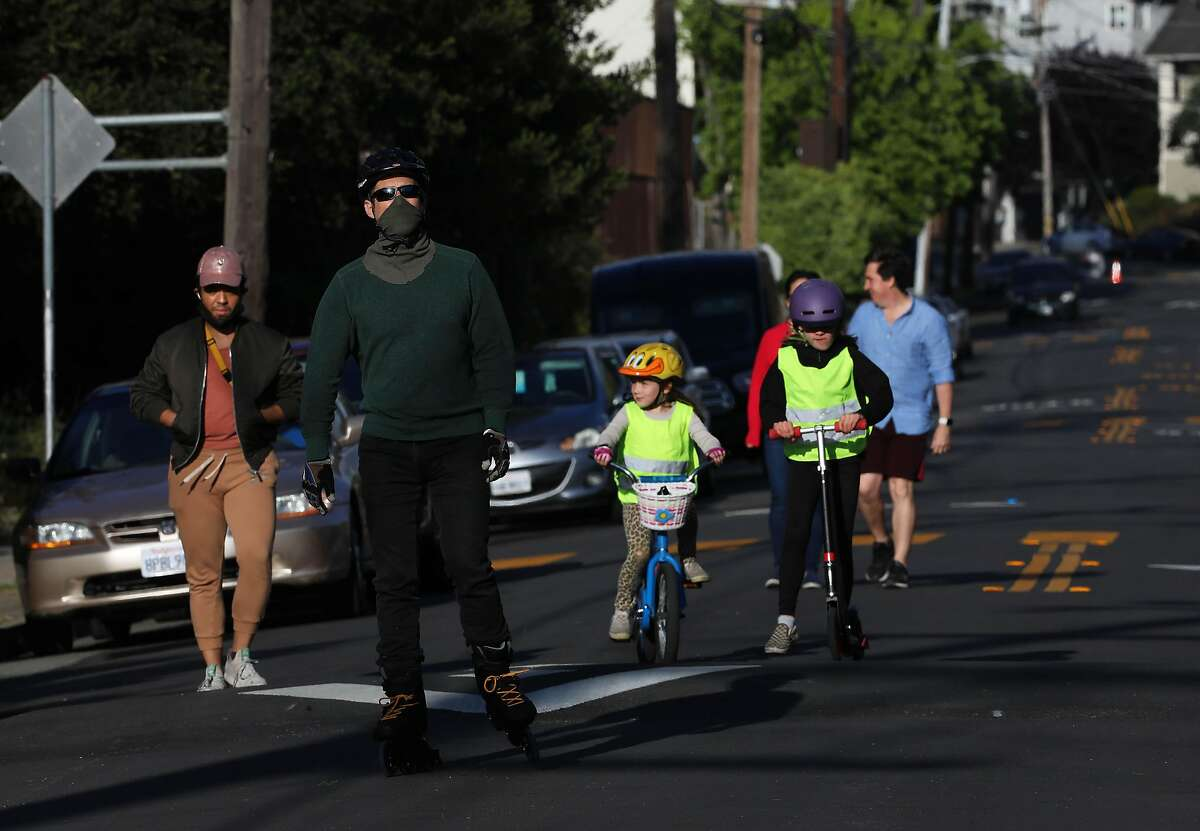 People exercise on 42th St., between Shafter and Webster, in Oakland, Calif., on Tuesday, May 12, 2020. Oakland has closed a number of streets to through traffic, the idea being that this will provide options for outdoor space to people with plenty of room for social distance and less need to be worried about cars hitting them.