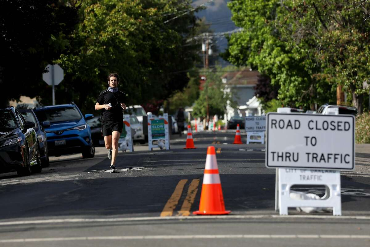 A runner exercises near the intersection of Webster St. and 40th St., in Oakland, Calif., on Tuesday, May 12, 2020. Oakland has closed a number of streets to through traffic, the idea being that this will provide options for outdoor space to people with plenty of room for social distance and less need to be worried about cars hitting them.