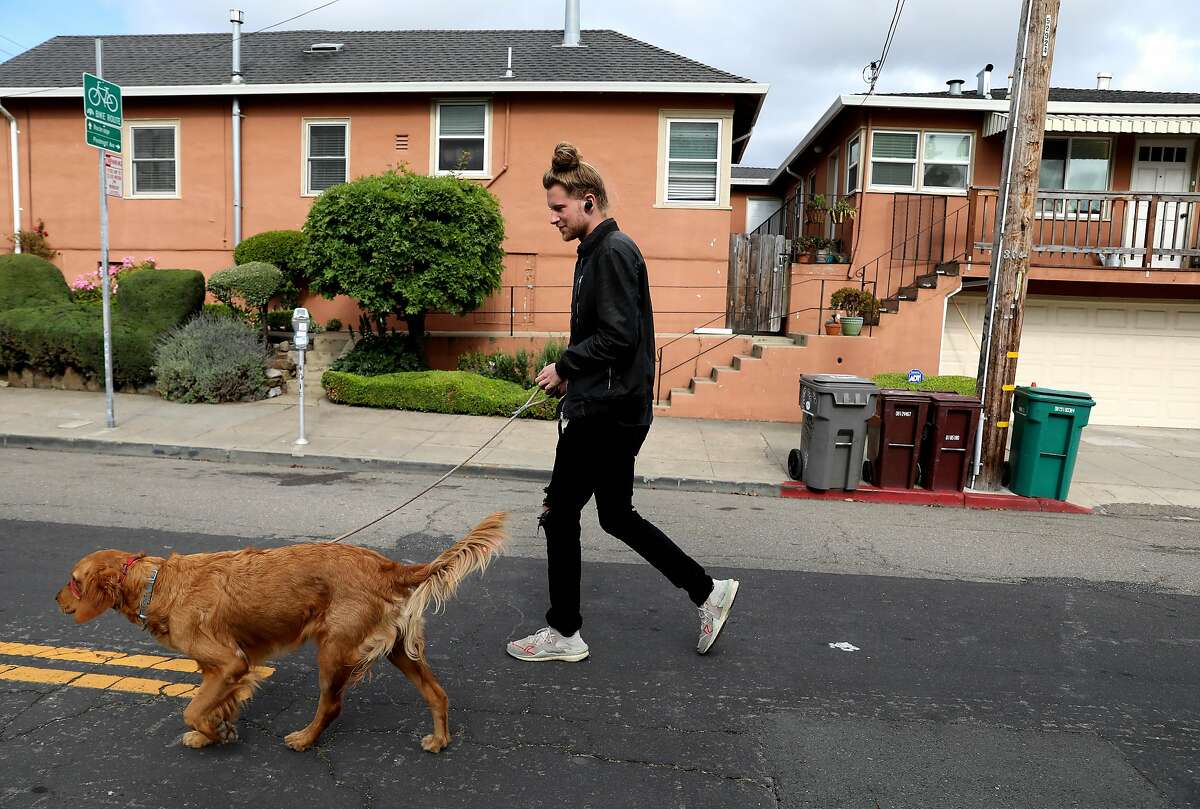 Jarvis Stack walks his dog, Bella, on Webster St., near 40th St., in Oakland, Calif., on Tuesday, May 12, 2020. Oakland has closed a number of streets to through traffic, the idea being that this will provide options for outdoor space to people with plenty of room for social distance and less need to be worried about cars hitting them.
