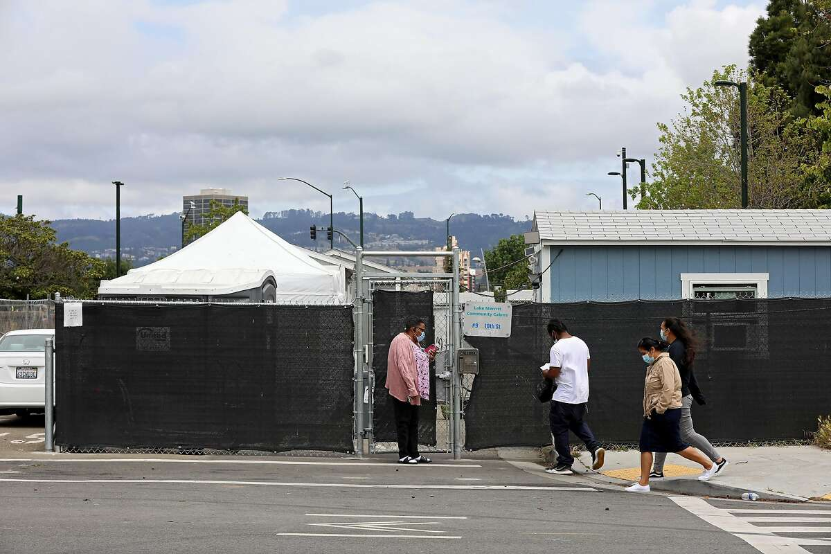 People meet at the entrance of the Lake Merritt Community Cabins, located at 9 10th St., in Oakland, Calif., on Tuesday, May 12, 2020. The unsheltered are housed in storage sheds at the site. According to reopening guidelines, counties can't open unless they can house 15 percent of its unsheltered population. The county has around 8,000 folks who are unsheltered. The Lake Merritt site was scheduled to be shut down at the end of the month, but Oakland has canceled those plans.