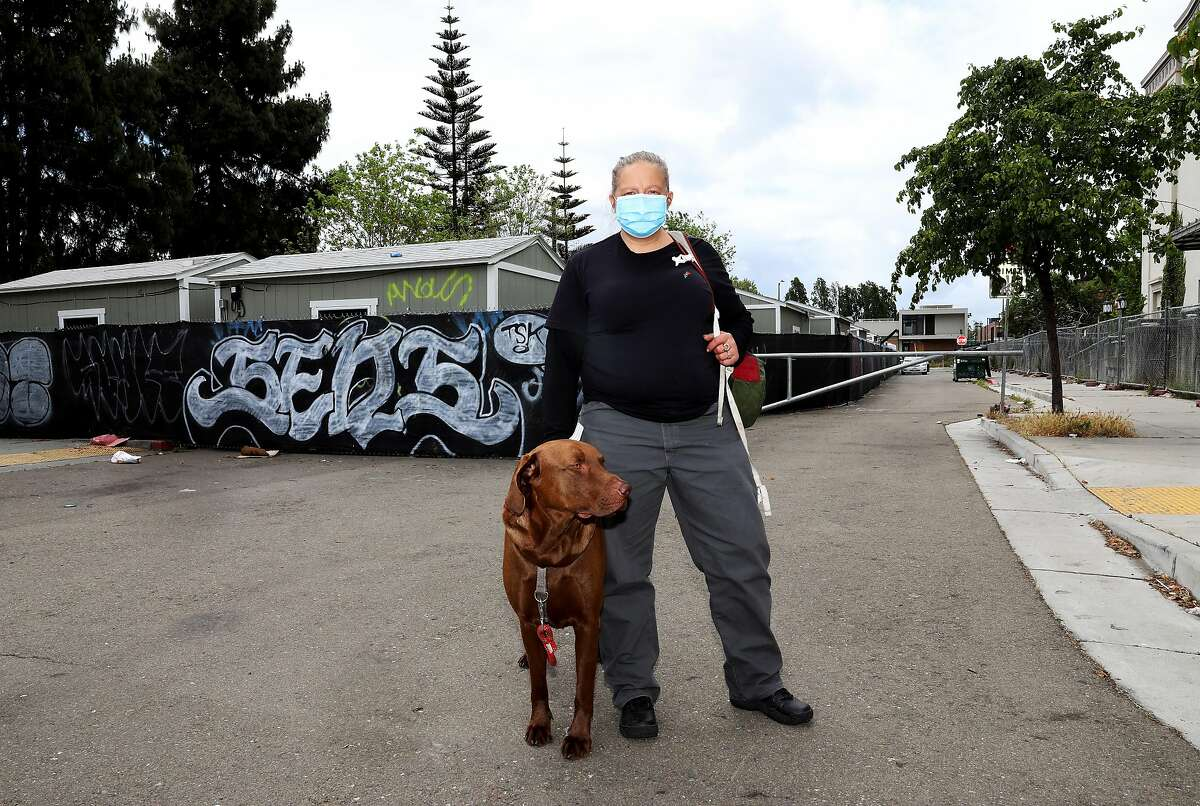 Jenn Oakley, 41, poses for a portrait with her dog Fattie as they stand outside the Lake Merritt Community Cabins, located at 9 10th St., in Oakland, Calif., on Tuesday, May 12, 2020. The unsheltered are housed in storage sheds at the site. According to reopening guidelines, counties can't open unless they can house 15 percent of its unsheltered population. The county has around 8,000 folks who are unsheltered. The Lake Merritt site was scheduled to be shut down at the end of the month, but Oakland has canceled those plans. Oakley is having trouble getting help to find something on her own.