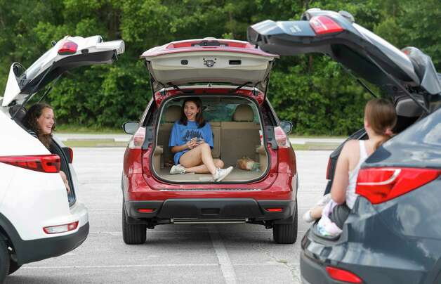 Julia Geer, center, shares a laugh with Piper Jones, left, and Addison Kaye as the trio visits using social distancing from the back of their vehicles at The Woodlands High School parking lot, Thursday, May 14, 2020, in The Woodlands. Photo: Jason Fochtman, Staff Photographer / 2020 © Houston Chronicle