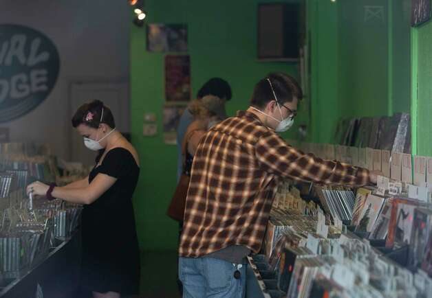Alexander Montis and Kellyn Evans shop at Vinal Edge Records Thursday, May 14, 2020, at the Heights in Houston. The record shop has been limiting four guests inside the shop, using hand sanitizer once they walk in and requiring them to wear a face cover. Photo: Yi-Chin Lee, Staff Photographer / © 2020 Houston Chronicle