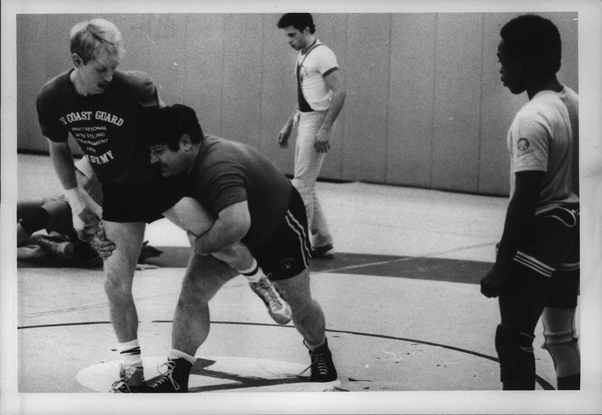 State University of New York, Albany Undated (SUNYA) wrestling coach Joe DeMeo makes move on Dave Averill as Shawn Sheldon watches. December 10, 1984 (Tom LaPoint/Times Union Archive)