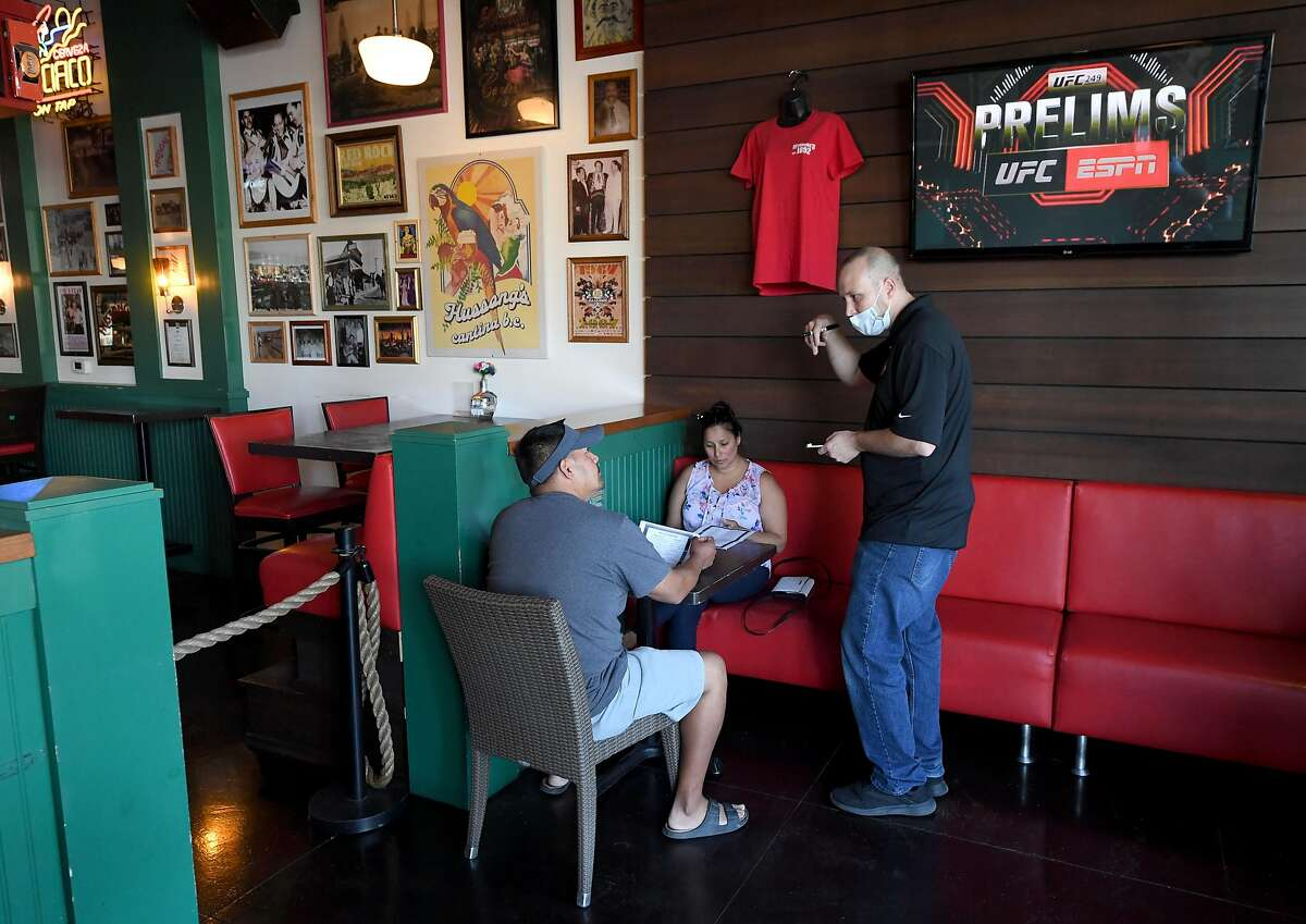 LAS VEGAS, NEVADA - MAY 09: General manager Steven Hanson (R) takes orders from Francisco Flores (L) and his wife Katia Flores of Nevada, the first customers allowed in Hussong's Cantina in Boca Park Fashion Village, as some businesses that were closed seven weeks ago to fight the spread of the coronavirus are allowed to reopen on May 9, 2020 in Las Vegas, Nevada. On Thursday, Nevada Gov. Steve Sisolak announced that under his Phase One reopening plan, the state would be allowing dine-in restaurants, hair and nail salons, some retail stores and other nonessential businesses to reopen today with strict social-distancing guidelines and occupancy restrictions in place. All employees who interact with the public are required to wear face coverings. Gaming establishments, including all hotel-casinos, are not reopening in Phase One. (Photo by Ethan Miller/Getty Images)