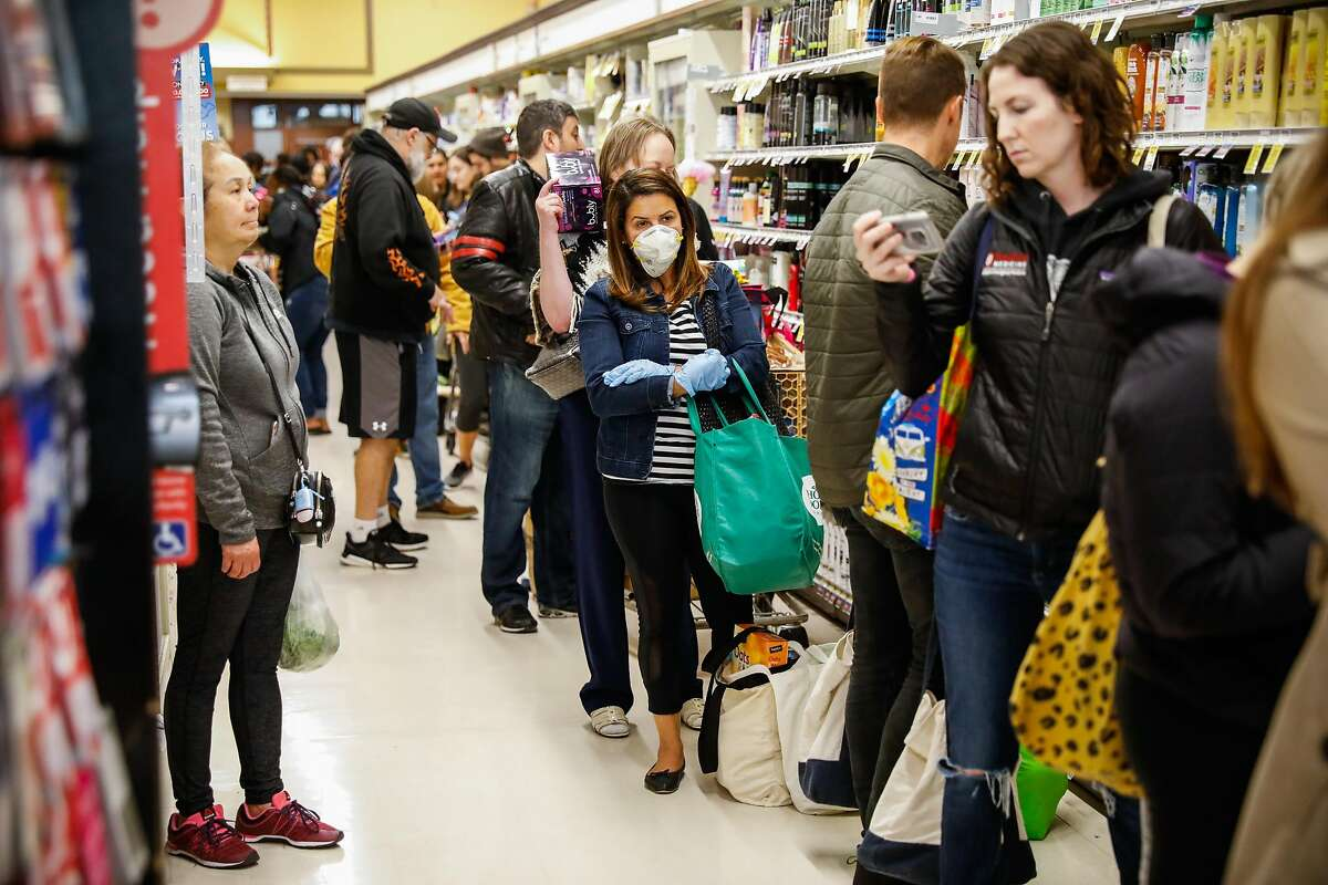 Dozens of people wait in line at Safeway after Mayor London Breed announced that six Bay Area counties would lockdown non-essential services due to the coronavirus on Monday, March 16, 2020 in San Francisco, California.