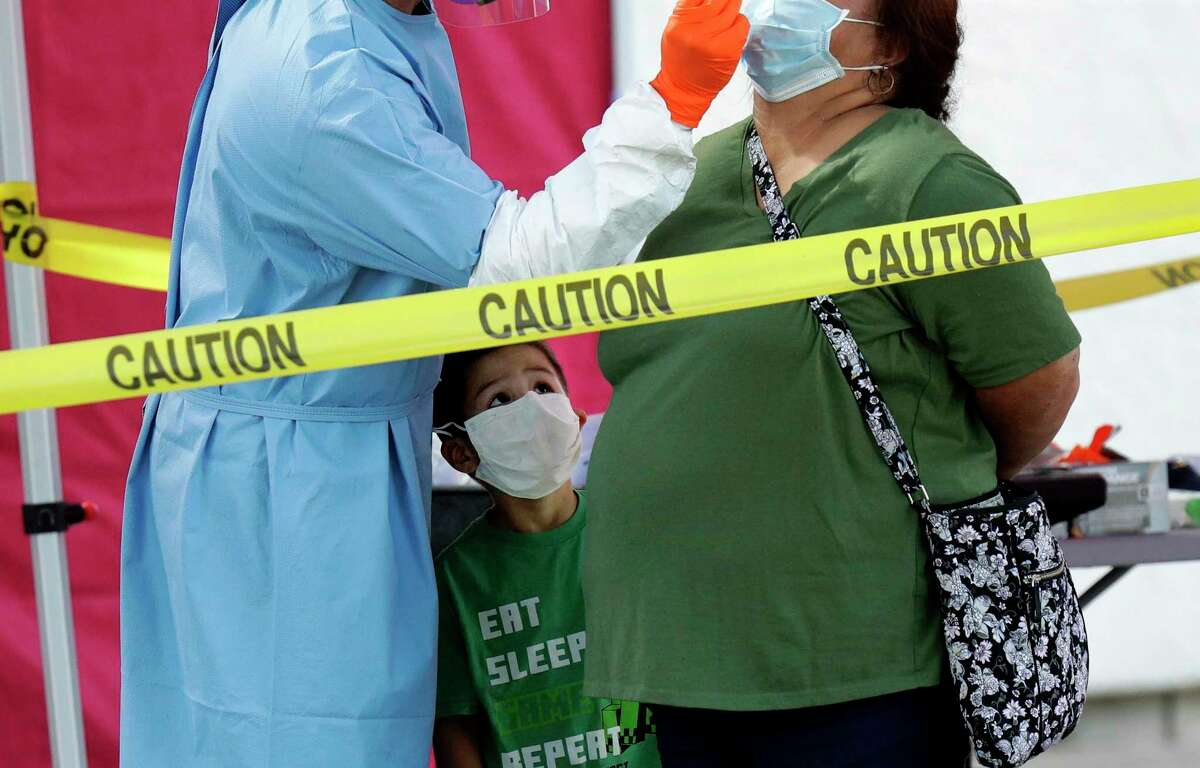 Jerry A. Mann, center, watches as his grandmother, Sylvia Rubio, is tested for COVID-19 by the San Antonio Fire Department at a free walk-up test site set up to help underserved and minority communities in San Antonio, Thursday, May 14, 2020. Texas attorney general Ken Paxton has warned officials in San Antonio, Austin and Dallas that the cities could face lawsuits if they do not relax coronavirus measures he says go further than state law allows. (AP Photo/Eric Gay)