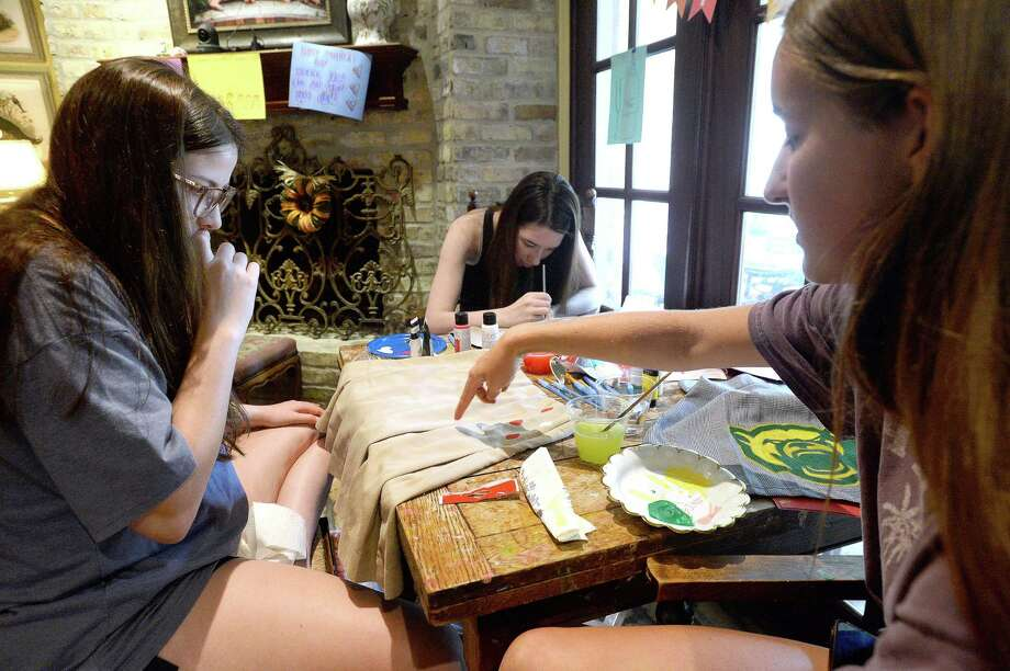 From left, Courtney Scritchfield, Ann Hill and Julia Phelan get together at Phelan's home Wednesday to begin decorating their Kelly High School uniforms with logos and lettering representing the colleges which they will be attending in the fall. It is a tradition for senior girls that has been going on for several years, and culminates with them wearing their transformed uniforms on the final day of classes. This year, the girls will gather safely outside the school for a photograph and to admire one another's handiwork as traditions and ceremonies at schools throughout the world have been upended amid COVID-19.   Photo taken Wednesday, May 13, 2020 Kim Brent/The Enterprise Photo: Kim Brent / The Enterprise / BEN