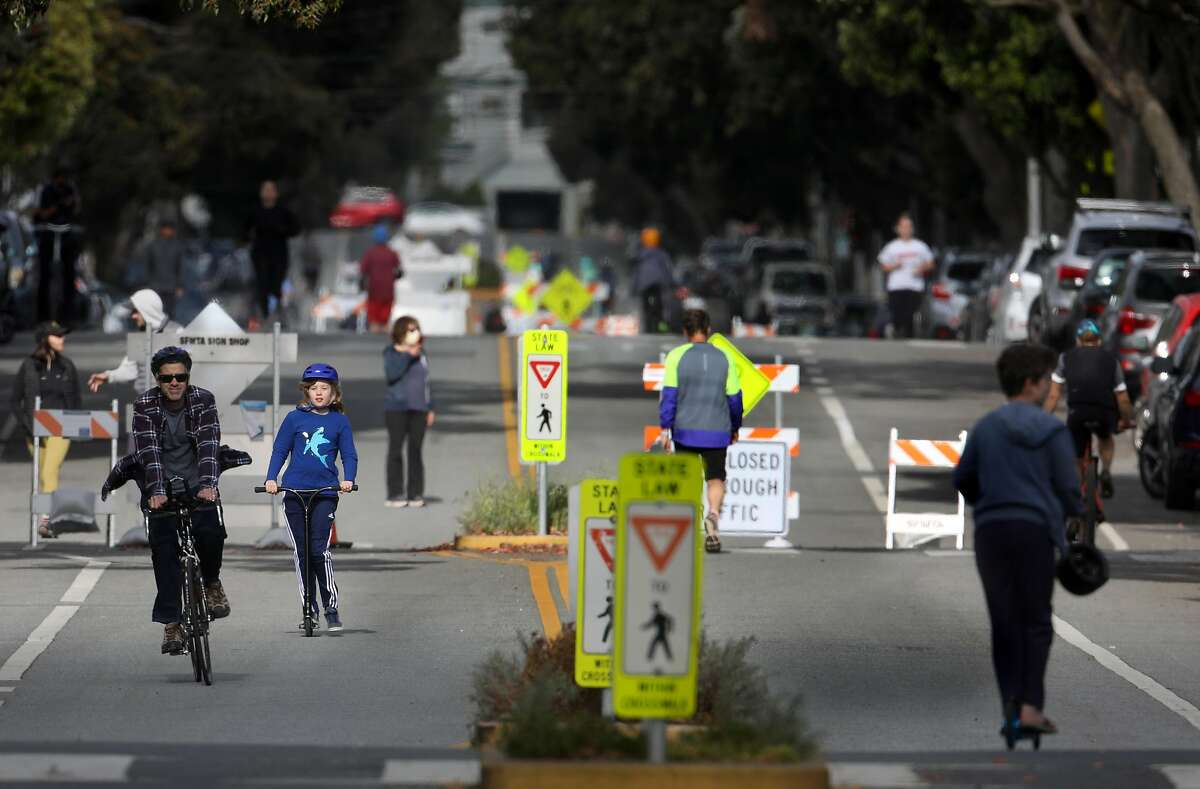Pedestrians take advantage of closed streets on Lake St. near 12th Ave. on Tuesday, May 12, 2020, in San Francisco, Calif. San Francisco has closed a number of streets to through traffic, the idea being that this will provide options for outdoor space to people with plenty of room for social distance and less need to be worried about cars hitting you.
