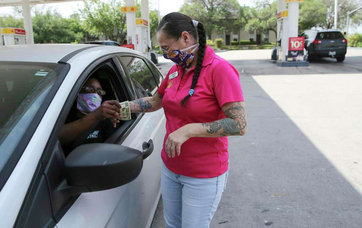 Longtime customer Etoy Brundige gives money to Laura Salazar Adams, manager of a Shell station in the Medical Center on Wednesday, Apr. 8, 2020. Salazar has a set up a system where folks with weak immune systems -- those undergoing chemo, dialysis, etc -- can call the station ahead of time. Employees will fill up their car, ring up groceries, etc, so the customers don't have to leave their cars. They even Lysol their credit cards and currency before returning it to their customer.