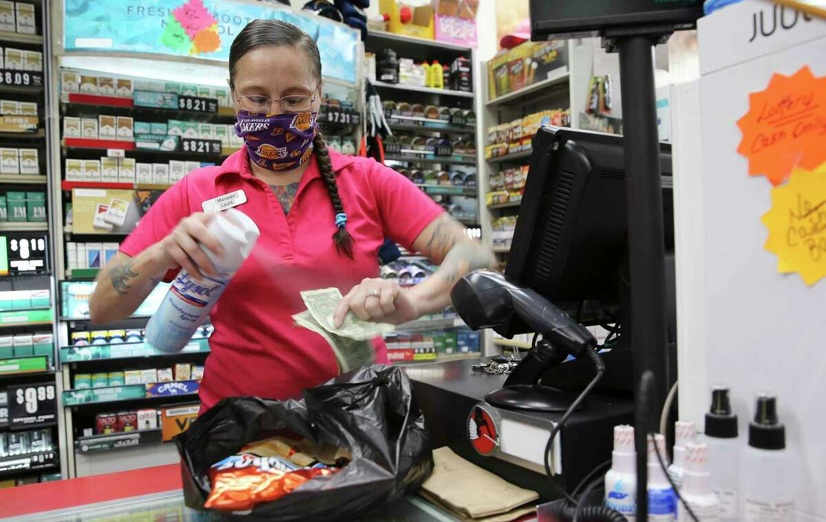 Laura Salazar Adams, manager of a Shell station in the Medical Center, sprays Lysol on some cash before she handing it to a customer waiting outside.
