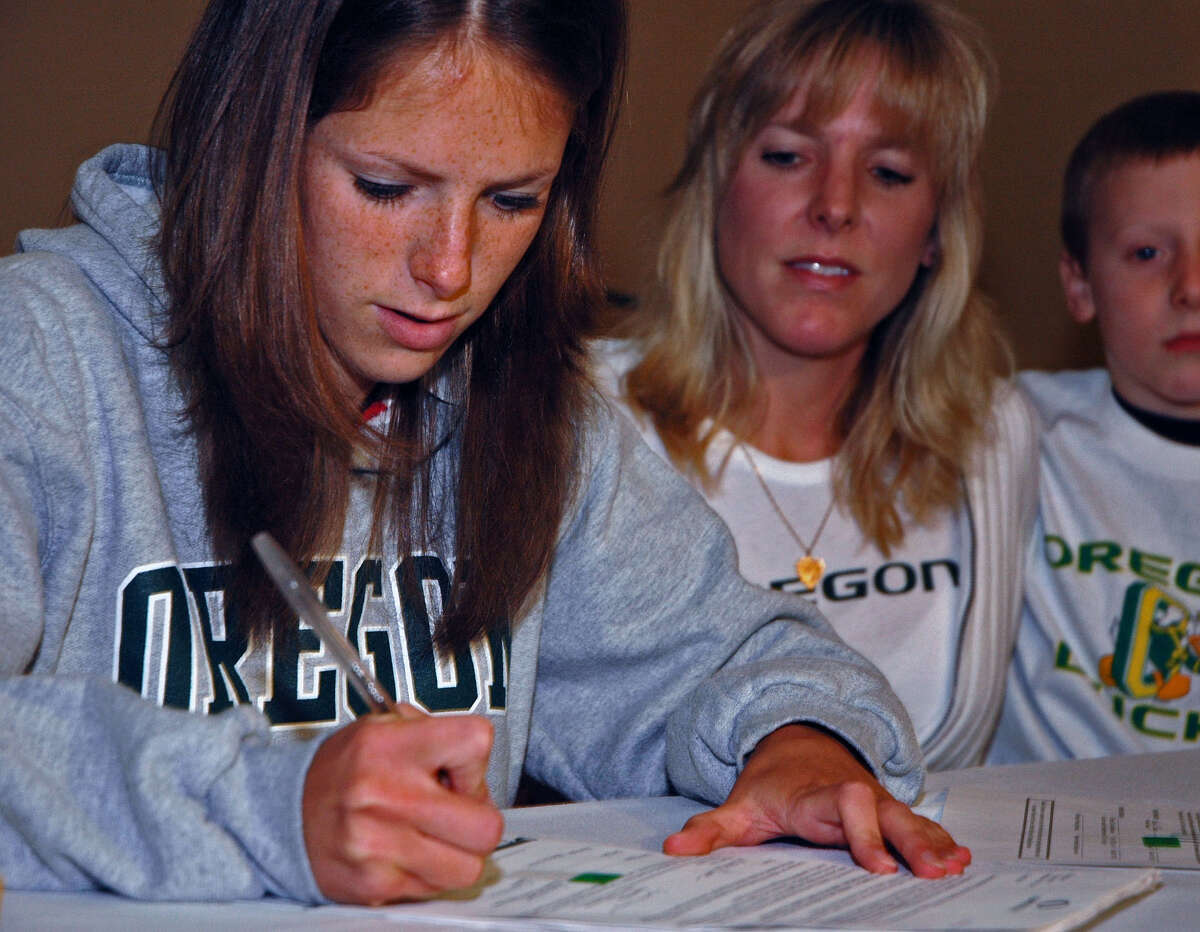 Times Union staff photo by John Carl D'Annibale Saratoga Springs runner Nicole Blood signs a national letter of intent to run at Oregon next fall as her mother Jill Buff and brother Matthew Buff, 8, look on during news conference Friday November 11, 2005