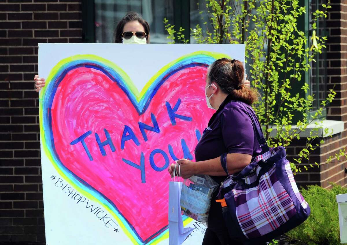Around 30 United Methodist Homes volunteers and administrators honor health care workers with a cheer line as the come and go during the change-of-shift at Bishop Wicke nursing home on Long Hill Ave in Shelton, Conn., on Thursday May 14, 2020. The cheer line was established by the Greater Valley Chamber of Commerce in Shelton.