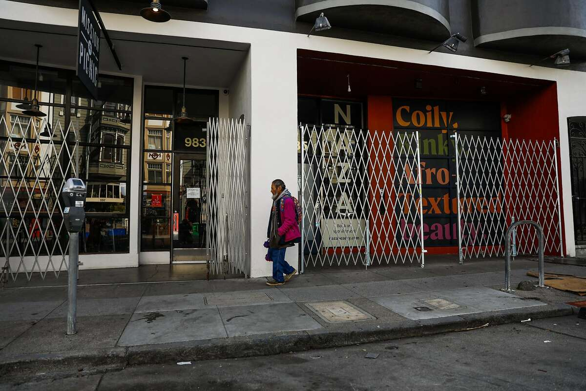 A pedestrian passes by closed up shops on Valencia Street on Tuesday, March 17, 2020 in San Francisco, California.