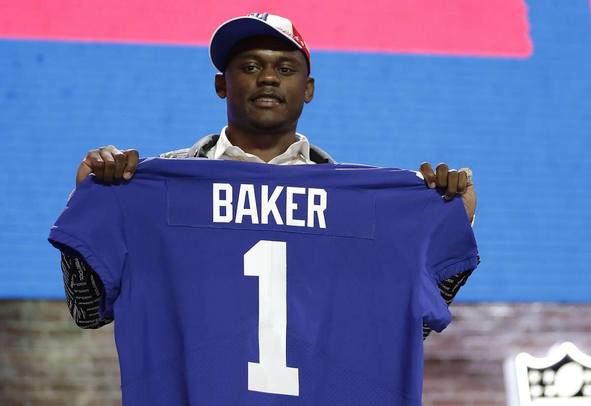 FILE - In this April 25, 2019, file photo, Georgia defensive back DeAndre Baker poses with his new jersey after the New York Giants selected him in the first round at the NFL football draft in Nashville, Tenn. Police in South Florida are trying to find Giants cornerback Baker and Seattle Seahawks cornerback Quinton Dunbar after multiple witnesses accused them of an armed robbery at a party. Miramar police issued arrest warrants for both men Thursday, May 14, 2020. (AP Photo/Mark Humphrey, File)