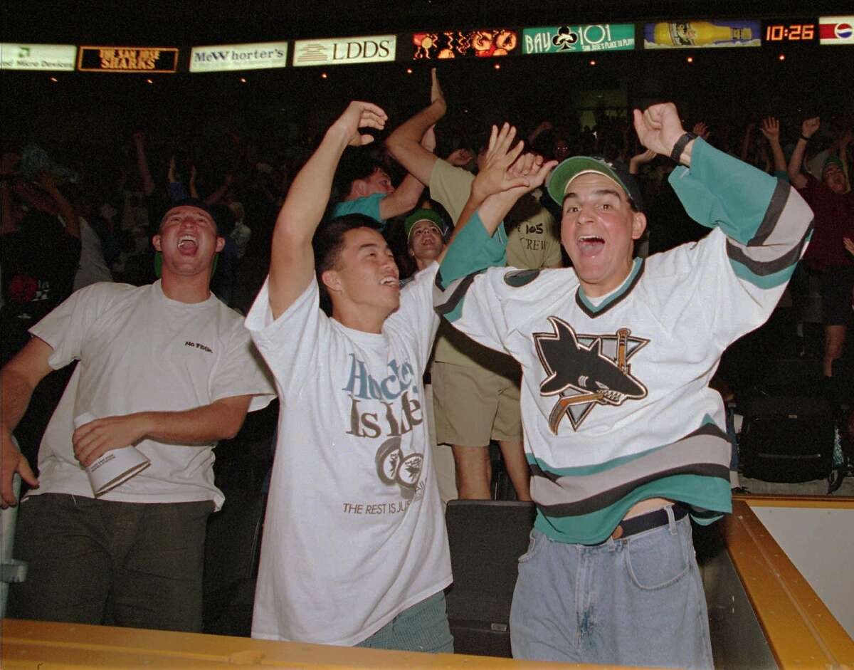 San Jose Sharks hockey fans Jeff Cohn, right, and Irwin Liu, center, react after the team scored in double overtime to win the first-round playoff series against the Calgary Flames, 5-4, on Friday, May 19, 1995. About 3,000 Sharks fans watched the game, which was played in Canada, on scoreboard video screens in the San Jose, Calif. arena. (AP Photo/ John Makely)