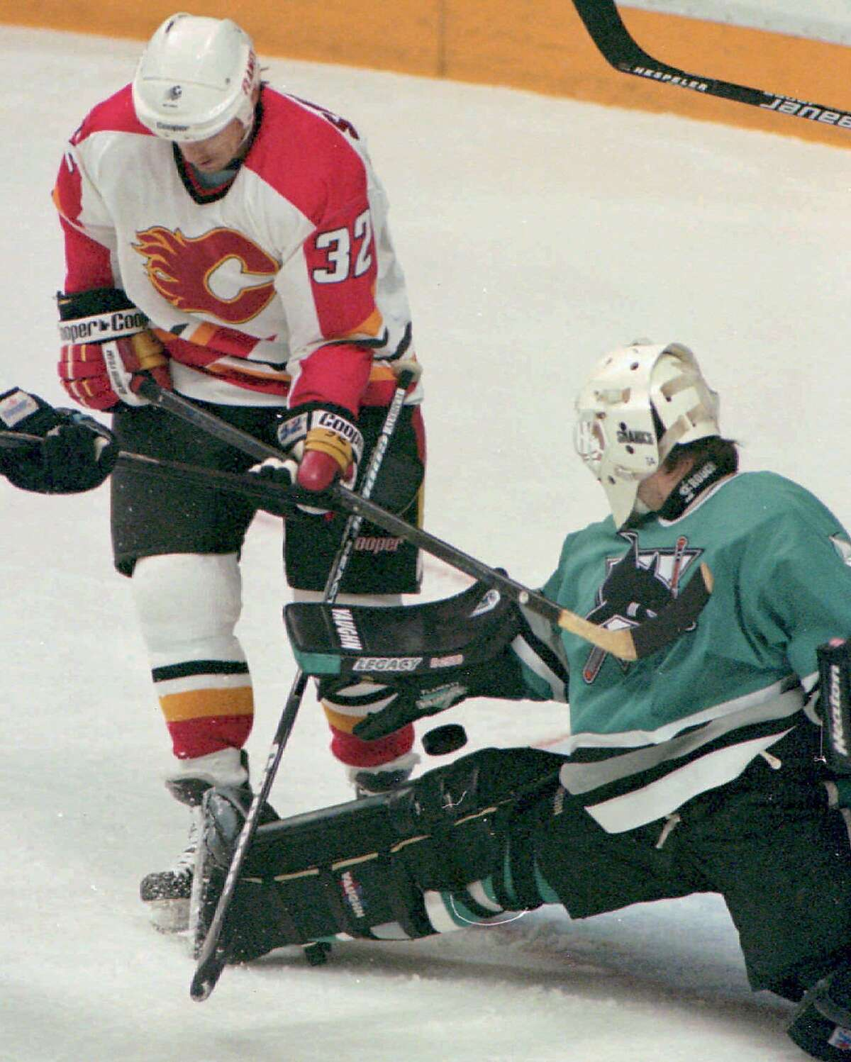 Calgary Flames winger Mike Sullivan presses San Jose Sharks goalie Wade Flaherty, right, as Flaherty makes the save during the first period of their playoff game in Calgary, Friday night, May 19, 1995. (AP Photo/Canadian Press, Dave Buston)