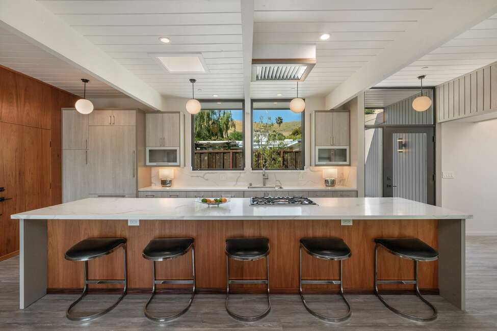 Just as in the original home, the kitchen is right off the entry, but now it is opened to the rest of the entertaining space and centers around a huge island with gas range.