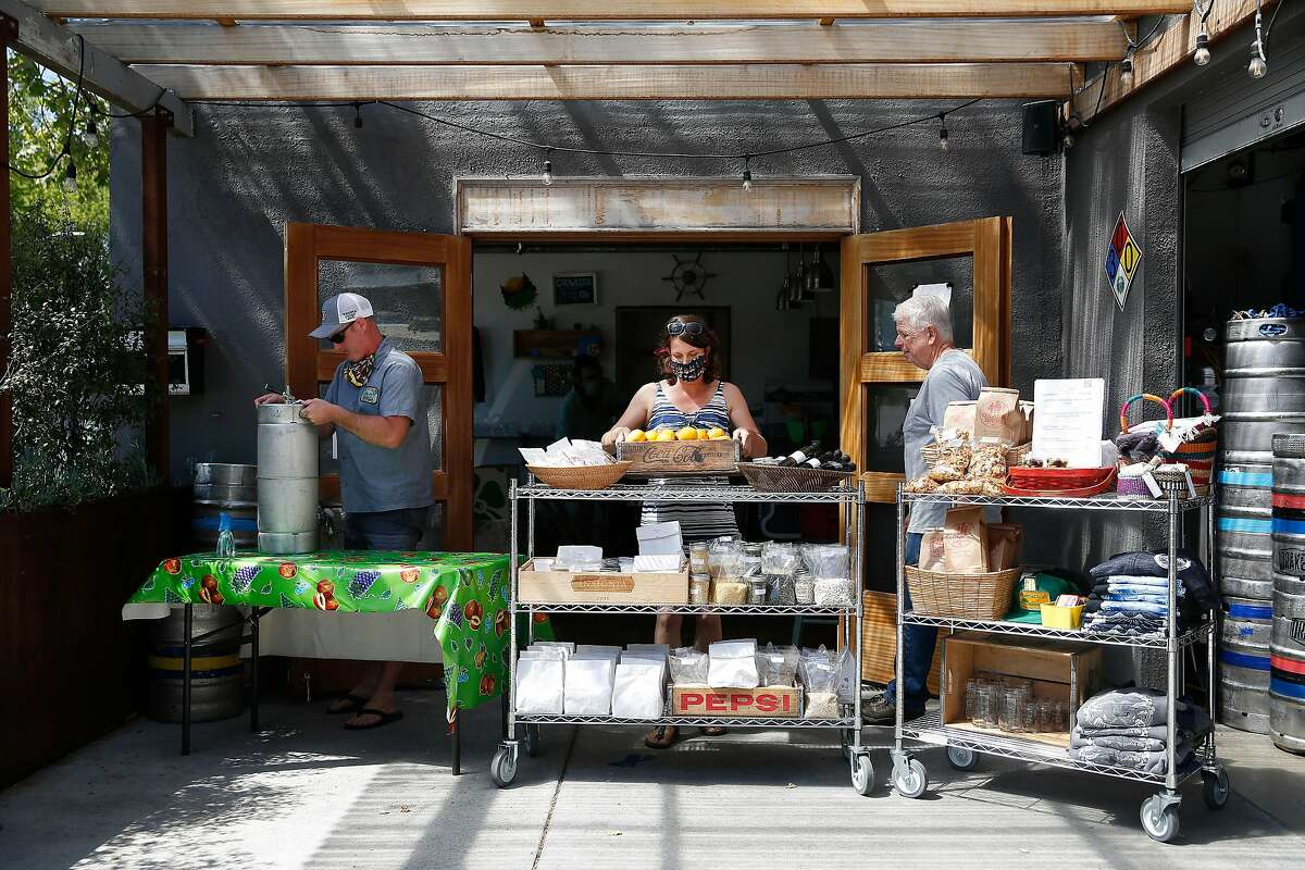 Scott Davidson (l to r), co-owner Ocean View Brew Works, Vonnie Davidson, co-owner Ocean View Brew Works, and David Orth, father of Vonnie Davidson, set up the store at Ocean View Brew Works on Wednesday, May 6, 2020 in Albany, Calif.