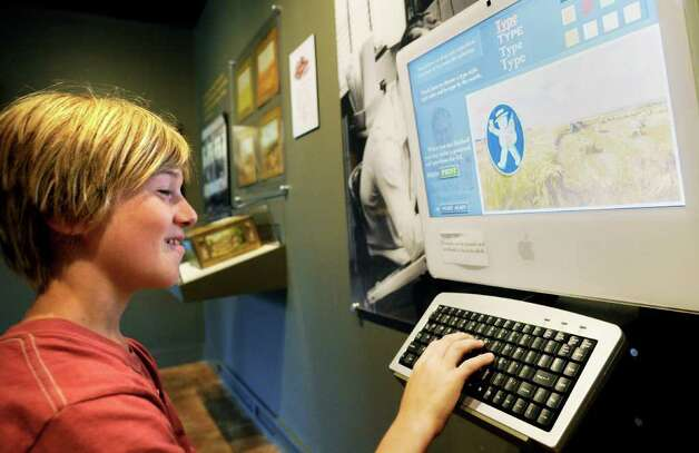 Solomon Palmer, age 10, of Fort Plain, in the interactive gallery at The Arkell Museum at Canajoharie on Tuesday, August 3, 2010.  He is using a computer to create his own Beech-Nut post card using themes and artwork from the company's advertising collection.  The card is then printed and given to the visitor to keep as a memento. (Luanne M. Ferris/Times Union) Photo: Luanne M. Ferris