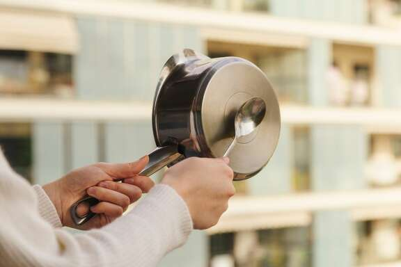 Stock photo of a casserole protest from the balcony against the government measures. Protester making noise hitting the pot
