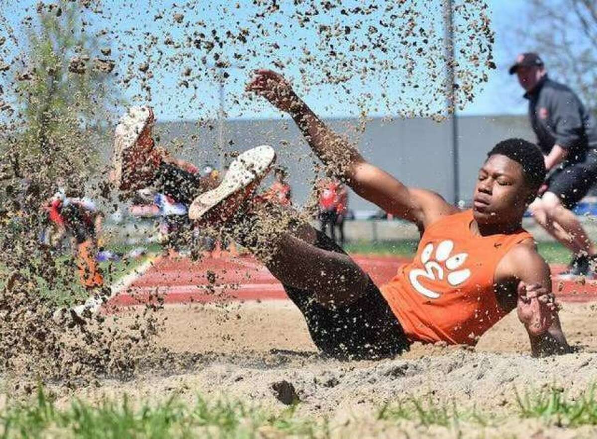 Edwardsville long jumper Kenyon Johnson lands after leaping 22-9 to finish second in the event at the Winston Brown Track and Field Invitational last year.