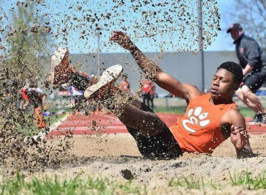 Edwardsville long jumper Kenyon Johnson lands after leaping 22-9 to finish second in the event at the Winston Brown Track and Field Invitational last year. Photo: Matt Kamp/The Intelligencer