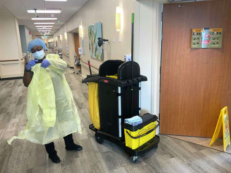 Mary Parker follows safety protocols for personal protective equipment (PPE) as she prepares to clean a patient room at Houston Methodist The Woodlands Hospital. Photo: Photo Courtesy Amy Barnett / Houston Methodist The Woodlands Hospital