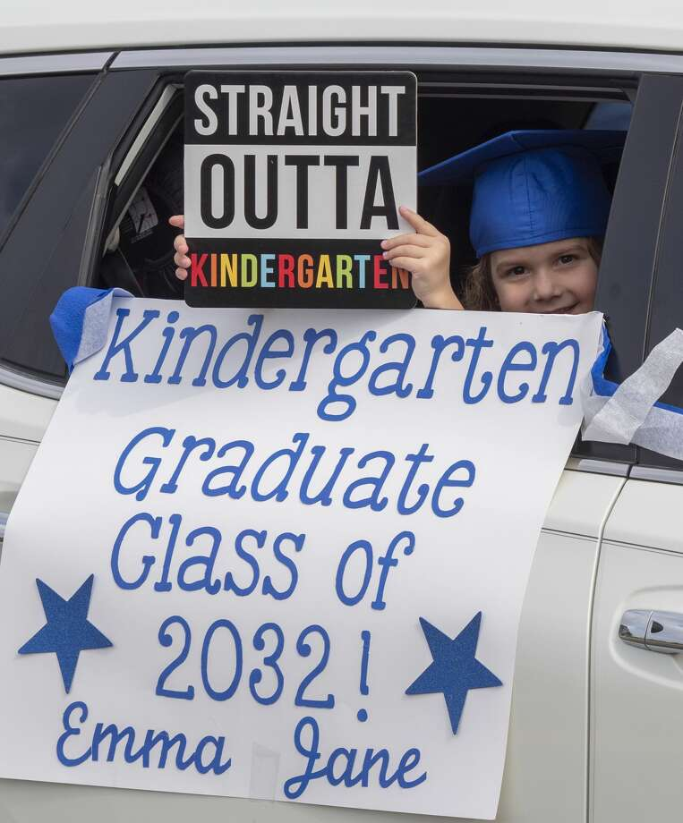 Emma Jane Wolf holds her sign out the window during graduation ceremonies 05/15/2020 as students and parents make their way along Trinity School parking lot for kindergarten graduation ceremony. Tim Fischer/Reporter-Telegram Photo: Tim Fischer/Midland Reporter-Telegram