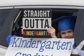 Emma Jane Wolf holds her sign out the window during graduation ceremonies 05/15/2020 as students and parents make their way along Trinity School parking lot for kindergarten graduation ceremony. Tim Fischer/Reporter-Telegram