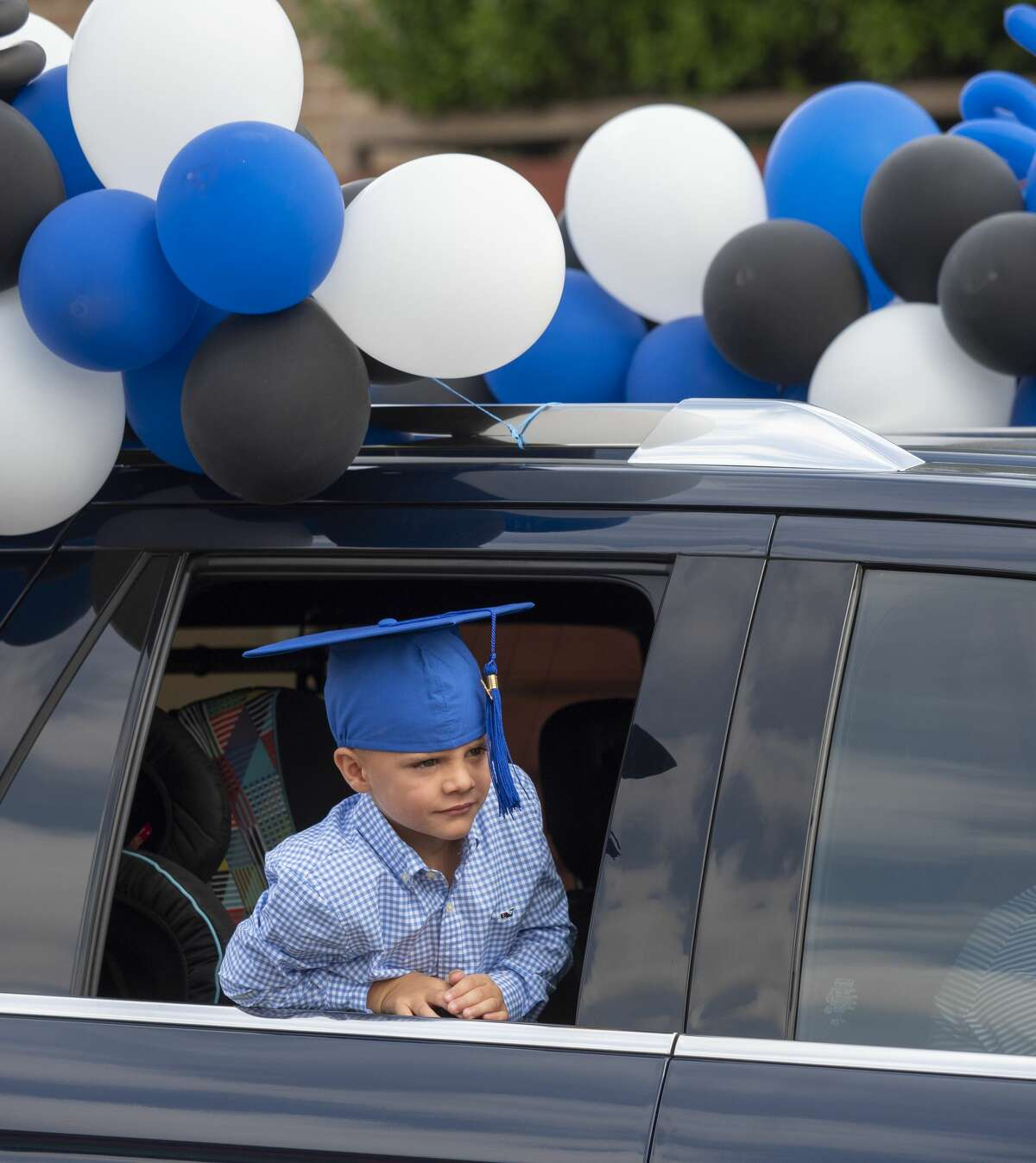 Hudson Miesner watches out his window during graduation ceremonies at Trinity School 05/15/2020 as students and parents make their way along Trinity School parking lot for kindergarten graduation ceremony. Tim Fischer/Reporter-Telegram