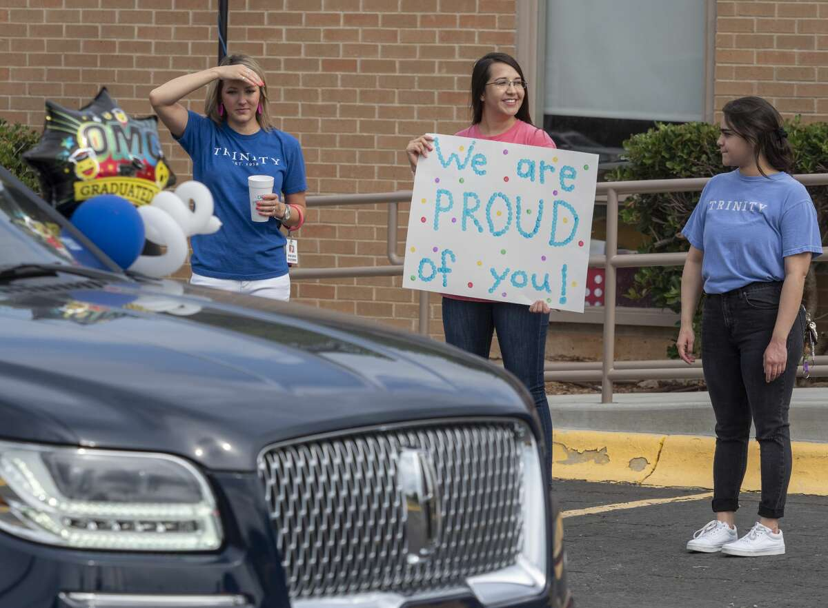 Trinity staff hold signs during graduation ceremonies 05/15/2020 as students and parents make their way along Trinity School parking lot for kindergarten graduation ceremony. Tim Fischer/Reporter-Telegram