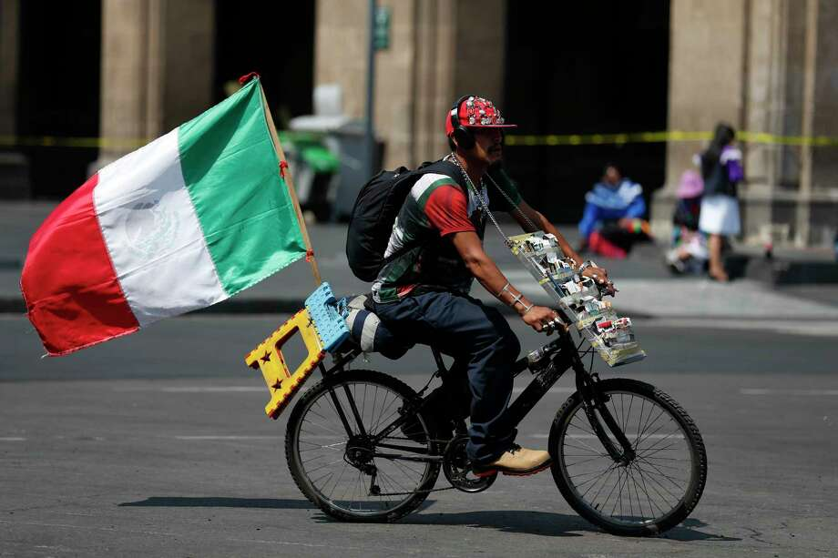 A man selling loose cigarettes rides a bike with a Mexican flag attached, as he passes roped-off government buildings in the Zocalo, Mexico City's main square, Monday, May 11, 2020. Health authorities concede that the real number of new coronavirus infections in the densely populated capital is many times higher than the official count, and authorities and experts agree that the worst is yet to come. Photo: Rebecca Blackwell, AP / Copyright 2020 The Associated Press. All rights reserved.