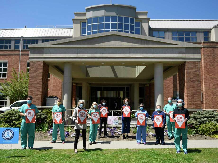 """Greenwich Historical Society leadership and hospital workers hold """"This Place Matters"""" signs in front of Greenwich Hospital in Greenwich, Conn. Tuesday, May 12, 2020. The Greenwich Historical Society is holding its fourth annual """"This Place Matters!"""" photo contest with this year's theme focusing on how the town is showing generosity and selflessness in combating the coronavirus pandemic. Photo: Tyler Sizemore / Hearst Connecticut Media / Greenwich Time"""