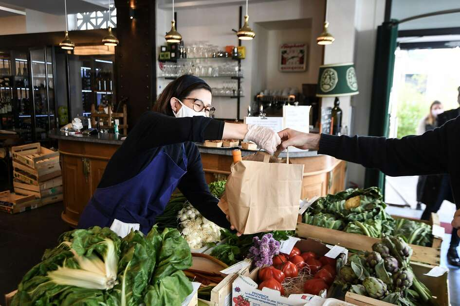 A customer buys food for take away at the L'Oseille restaurant where people can also buy fresh fruits and vegetables, on May 15, 2020 in Paris, a few days after France eased lockdown measures taken to curb the spread of the COVID-19 pandemic, caused by the novel coronavirus. (Photo by ALAIN JOCARD / AFP) (Photo by ALAIN JOCARD/AFP via Getty Images)