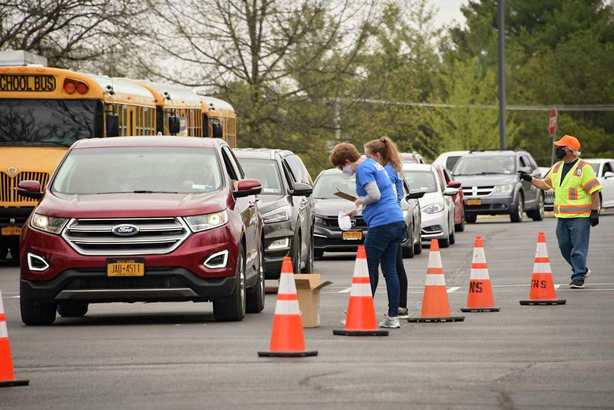 People in cars are checked in at a food pantry at Clayton A. Bouton High School on Friday, May 15, 2020 in Voorheesville, N.Y. Ballston Spa National Bank, in conjunction with the Regional Food Bank of Northeastern New York and the Voorheesville School District hosted the drive-thru food pantry for area families and individuals in need of food and supplies. (Lori Van Buren/Times Union)