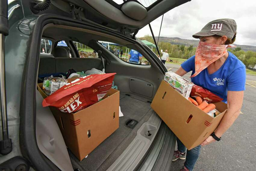 Volunteer Jill Robbins loads food into the back of a car at a food pantry at Clayton A. Bouton High School on Friday, May 15, 2020 in Voorheesville, N.Y. Ballston Spa National Bank, in conjunction with the Regional Food Bank of Northeastern New York and the Voorheesville School District hosted the drive-thru food pantry for area families and individuals in need of food and supplies. (Lori Van Buren/Times Union)