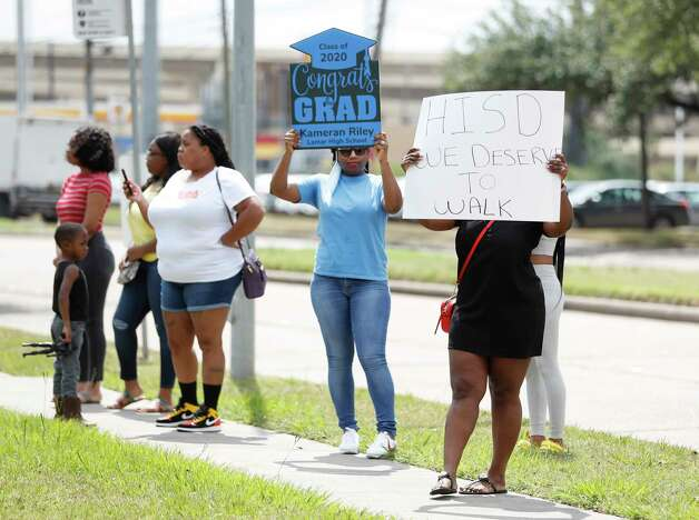 Parents and students hold signs asking for real graduations as Houston ISD Interim Superintendent Grenita Lathan held a press conference in front of the Hattie Mae White Educational Support Center, in Houston, Friday, May 15, 2020. Photo: Karen Warren, Staff Photographer / © 2020 Houston Chronicle