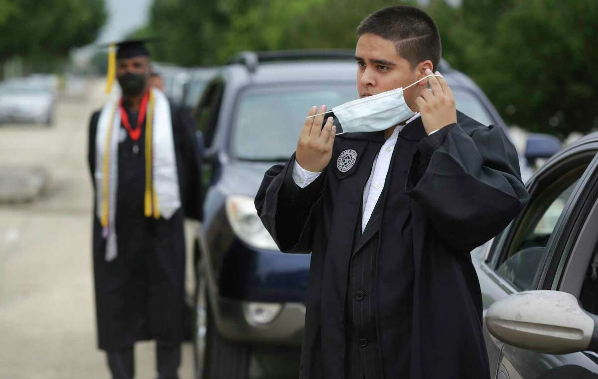 Giovanni Ramirez, right, puts on his mask as he and fellow graduate Larry Mosley, left, wait by their cars during the curbside graduation ceremony at Texas A&M University San Antonio on May 15.