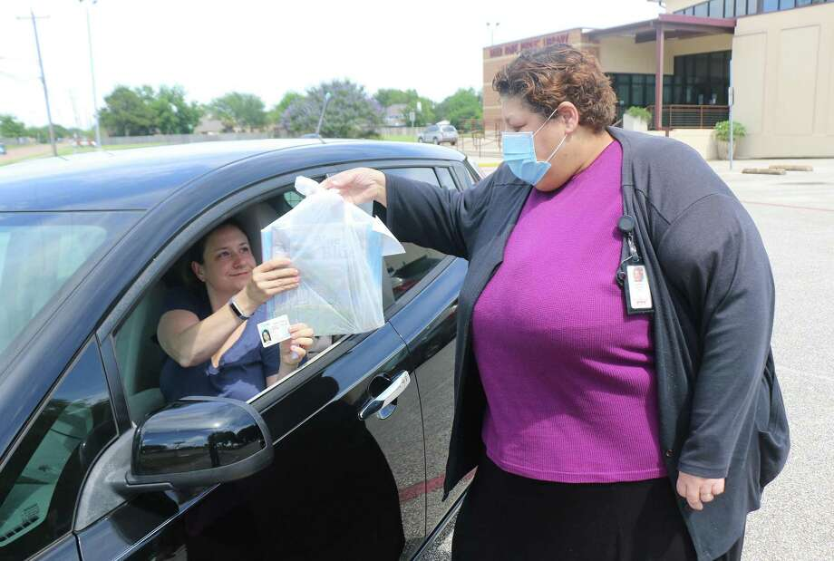 Rita Hlavacek shows her driver's license to Deer Park Library clerk Elsa Rivera to pick up the books she had reserved at the library. Hlavacek says she loves the convenience of the curbside delivery. Photo: David Taylor / Staff Photo