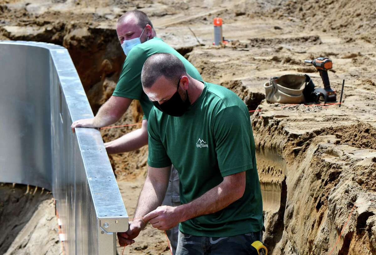 Workers from Alpin Haus install a residential swimming pool under the first day of lifting state coronavirus restrictions in the Mohawk Valley zone on Friday, May, 15, 2020, in Gloversville, N.Y. (Will Waldron/Times Union)