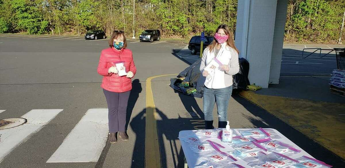 State Rep. Christie Carpino and Portland First Selectwoman Susan S. Bransfield hand out face masks outside the Adams IGA on Marlborough Street in Portland.