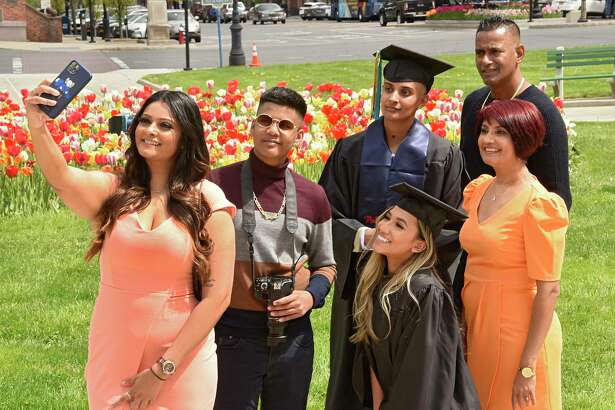 Back row from left, Shauneille Sinanan takes a selfie with Kyle Kissoon, University at Albany graduate Sherelle Sinanan, Clyde Sinanan, front row from left, University at Albany graduate Tunisha Haque, and Shanti Sinanan outside the Capitol on Friday, May 15, 2020 in Albany, N.Y. The family was taking photos of the grads in their caps and gowns by the tulips today since there isn't a traditional commencement ceremony. (Lori Van Buren/Times Union)