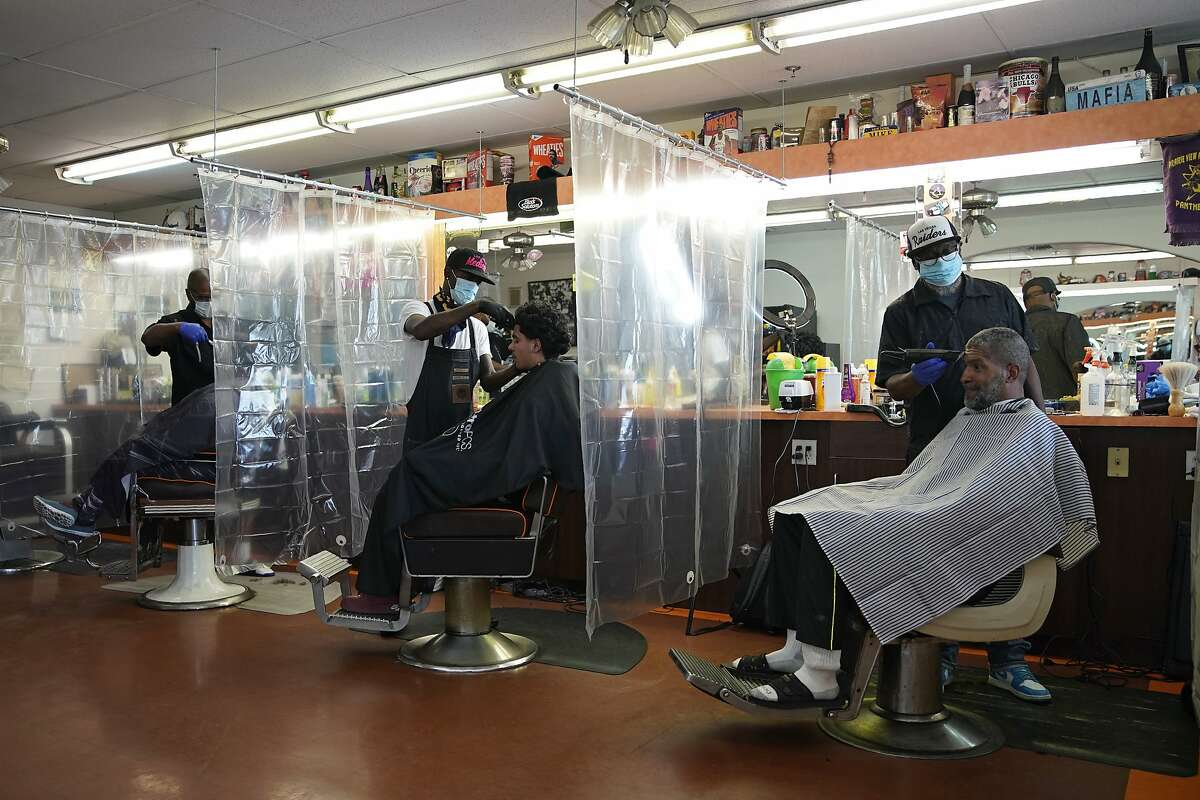 Plastic sheets separate customers at A Cut Above the Rest barber shop, Saturday, May 9, 2020, in Las Vegas. Saturday was the first day restaurants, salons and other nonessential businesses were allowed to start reopening after restrictions were imposed seven weeks earlier to help stop the spread of the new coronavirus. (AP Photo/John Locher)