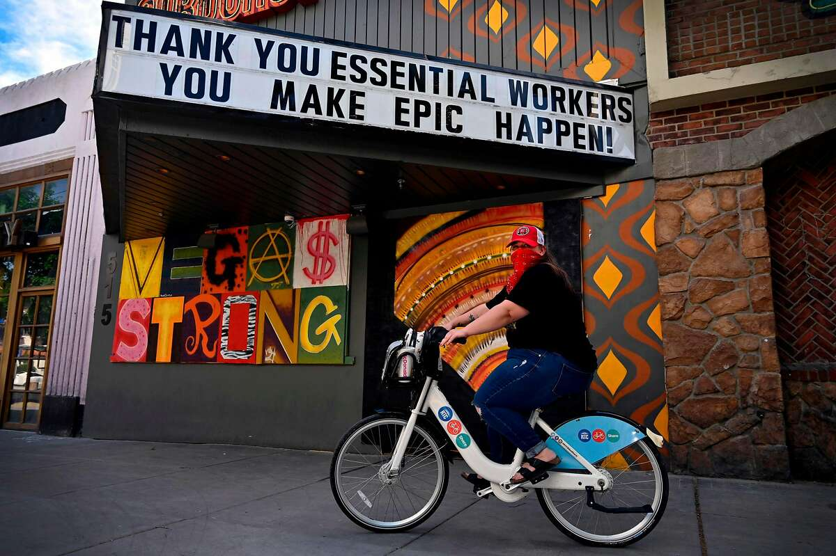 School teacher Mikala Miles of Las Vegas rides a bicycle along Fremont Street as the coronavirus continues to spread across the United States, on April 25, 2020 in Las Vegas, Nevada. - Nevada Gov. Steve Sisolak ordered a mandatory shutdown of nonessential businesses, including all casinos, in the state through at least April 30, 2020 to help combat the spread of the virus. The World Health Organization declared the coronavirus (COVID-19) a global pandemic on March 11th. (Photo by David Becker / AFP) (Photo by DAVID BECKER/AFP via Getty Images)