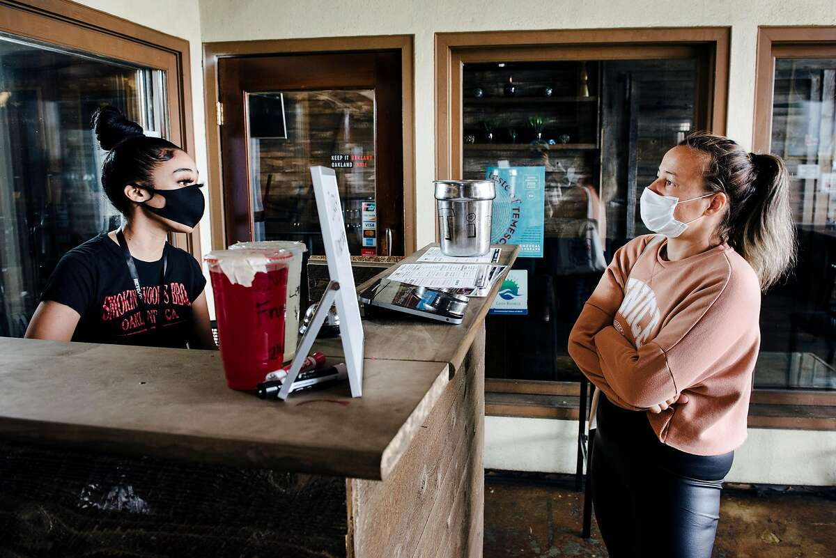 Server Myah Ortiz, left, takes a to-go order from Niki Nagy of Concord, at Smokin Woods BBQ in Oakland, Calif, on Thursday, May 14, 2020.