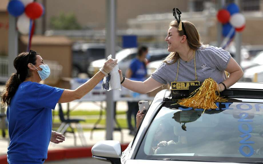 Jessica Donovan receives a graduation gif basket during the Oak Ridge High School senior graduation sendoff, Friday, May 15, 2020, in Oak Ridge. Members of the Class of 2020 went through the drive-in parade to pick up cap and gowns, yard signs, gifts and received well wishes from teachers and staff. Photo: Jason Fochtman/Staff Photographer / 2020 ? Houston Chronicle